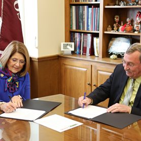 This is a photo of Dr. Boggess and Mr. Hicks signing the MOU in the President's Office. They are seated at a conference table.