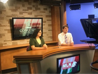 Students sitting at the anchor desk for television