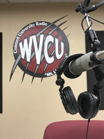 Photo of the WVCU logo and earphones over a microphone