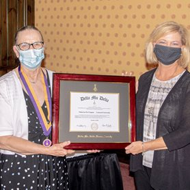 Photo of Dr. Davis and Dr. Robinett holding the charter for the new chapter.