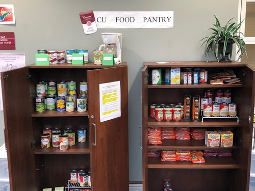 Picture of two cabinets in Rahall Technology Center atrium that house the CU Food Pantry. Doors are open showing the stock of canned goods and other non-perishable food items available for students in need.